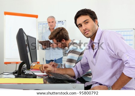 Serious trainee sitting in classroom - stock photo