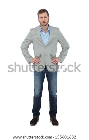 Serious trendy man posing with hands on hips on white background - stock photo