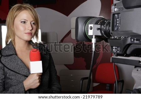 serious TV reporter in live transmission  looking at the video camera - stock photo