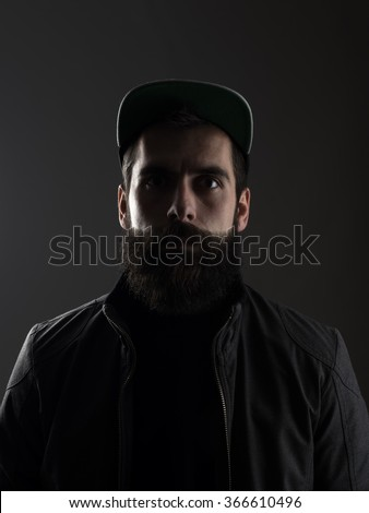 Serious unconventional bearded man wearing baseball cap staring at camera.  Low key dark shadow portrait over black background.  - stock photo