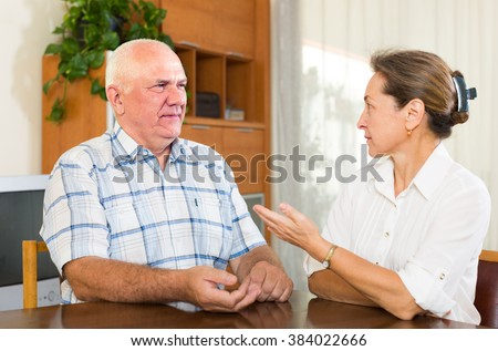 Serious unhappy mature couple talking in home interior. Focus on man - stock photo