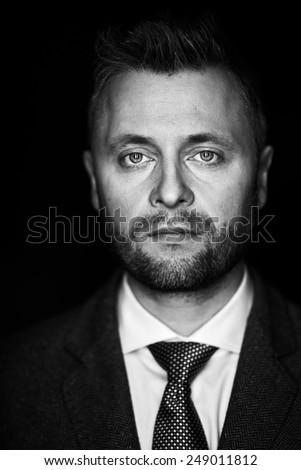 Serious unshaven man looking at camera - stock photo