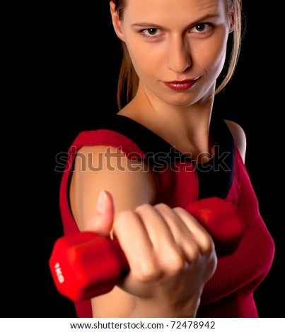 Serious woman athlete showing red dumbbell on black background - stock photo