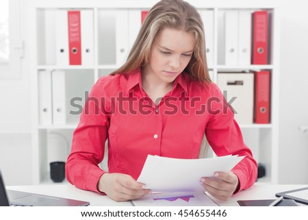 Serious woman examines documents with charts - stock photo