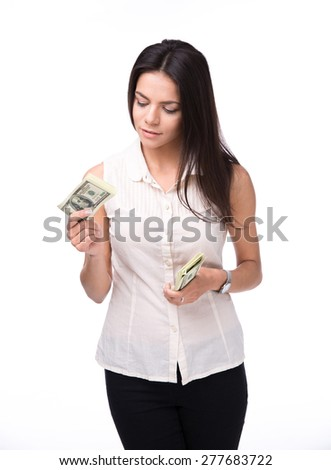 Serious woman holding bills of dollar over white background - stock photo
