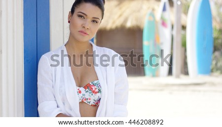 Serious woman in bathing suit near surfboards