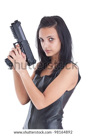 Serious woman is aiming a handgun, she is looking at the camera. Pretty girl is wearing a black leather