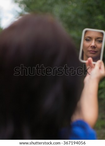 serious woman looking at the mirror - stock photo