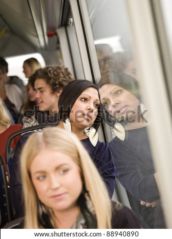 Serious woman on the bus with large group of people - stock photo