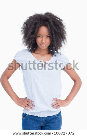 Serious woman placing her hands on her hips against a white background