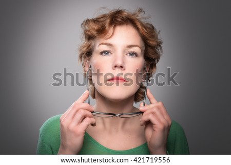 Serious woman - Strong and determined red haired female holding glasses - stock photo