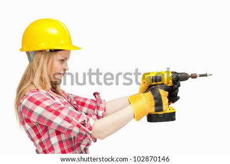 Serious woman using an electric screwdriver against white background - stock photo