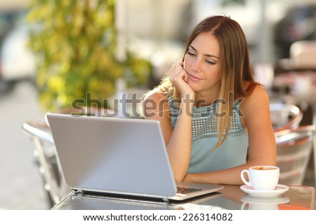 Serious woman watching a laptop in a restaurant terrace with an unfocused background - stock photo