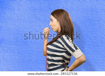 Serious woman with a whistle. Over blue background - stock photo