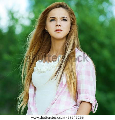 serious woman young beautiful park your hands pocket - stock photo