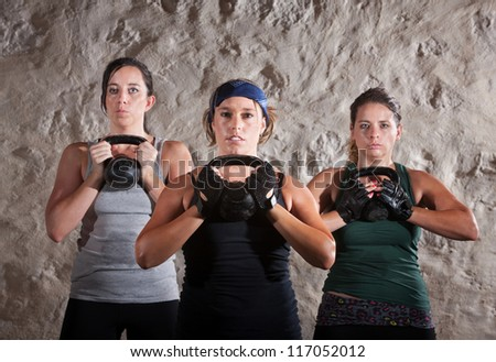 Serious women lifting kettlebells for boot camp style workout - stock photo