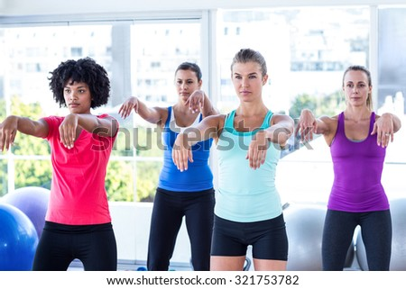Serious women with arms stretched forward in fitness studio