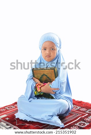Serious Young Asian Muslim girl in blue hijab hold a Al Quran. - stock photo