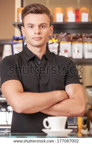 serious young barista behind counter. handsome young man and cup of coffee