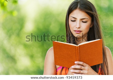 serious young, beautiful girl holding an open book, read background summer green park - stock photo