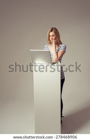 Serious Young Blond Woman Using her Laptop Computer on a Platform While in Standing Position, Isolated on Brown. - stock photo