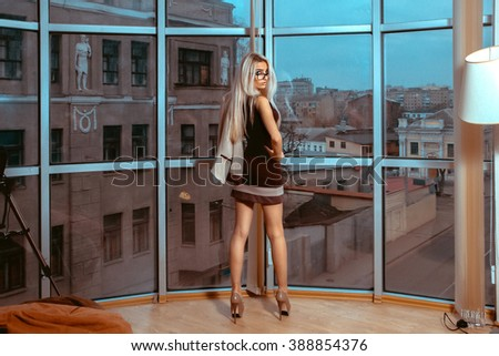 Serious young blonde business lady posing near large window with city views. City views behind the window in the office. Business concept. - stock photo