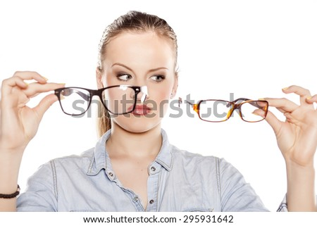serious young blonde compares glasses - stock photo