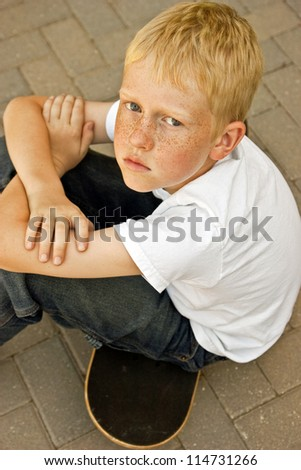 Serious young boy sitting on a skateboard with his arms crossed