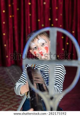 Serious Young Boy Wearing Clown Make Up Aiming Over Sized Rifle Gun Toward Camera and Standing on Stage in front of Red Curtain - stock photo