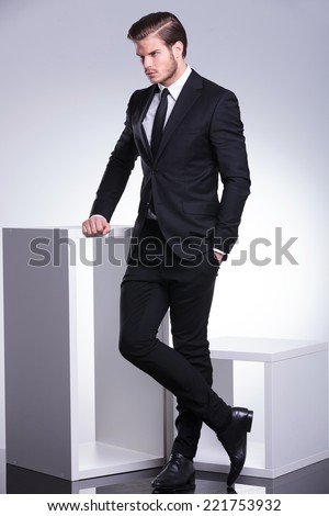 Serious young business man holding one hand on a white table while looking away from the camera. - stock photo