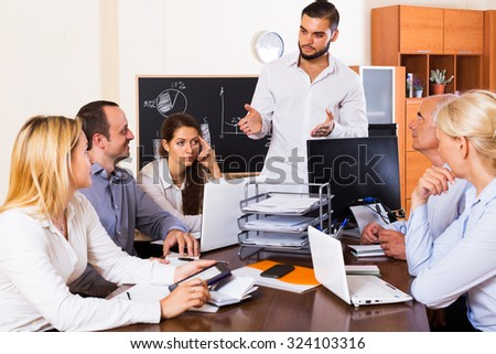 Serious young business people during conference call indoors - stock photo
