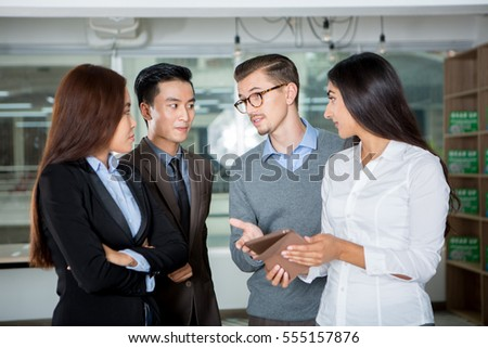 Serious young business people talking in office