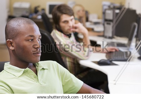 Serious young businessman at desk with colleagues in background - stock photo