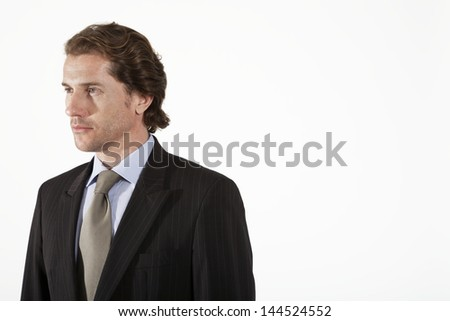 Serious young businessman looking away against white background - stock photo