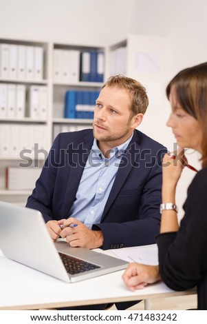 Serious young businessman sitting listening and watching something off screen as he sits sharing a laptop with a female colleague