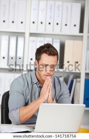 Serious young businessman with hands on chin using laptop at office desk - stock photo