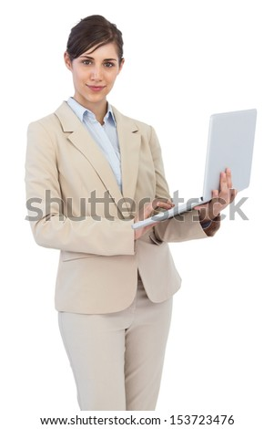 Serious young businesswoman holding laptop against white background