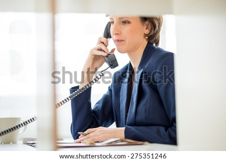 Serious Young Businesswoman Sitting at her Desk Answering a Telephone Call from a Customer. - stock photo