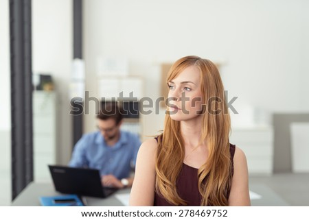 Serious young businesswoman standing thinking with a contemplative expression as a colleague works in the background - stock photo