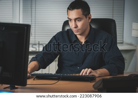 Serious young caucasian businessman in his office - stock photo