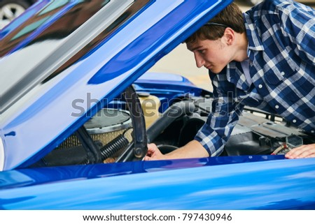 Serious young Caucasian man wearing checked shirt opening bonnet and looking under hood of his car