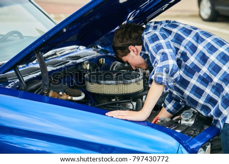 Serious young Caucasian man wearing checked shirt standing at open hood and repairing car his broken car