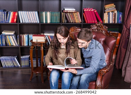 Serious Young Couple Sitting on a Brown Elegant Chair Reading a Book in Front of Bookshelves. - stock photo