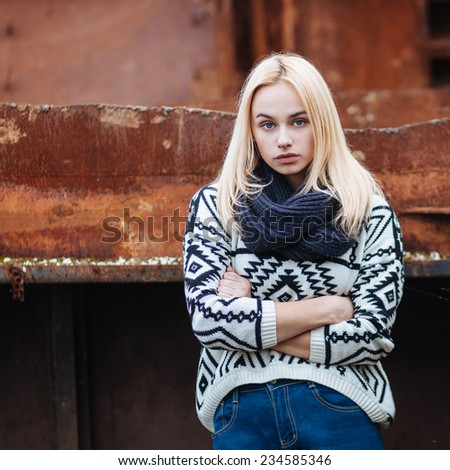 Serious young cute lady in sweater and scarf outdoors portrait - stock photo