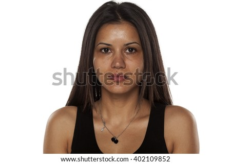 Serious young dark-skinned pretty woman without makeup - stock photo