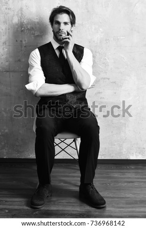 serious young fashion business man in classy suit and tie sitting on chair on beige background