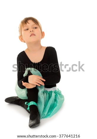 Serious young gymnast sitting on the floor - Isolated on white background - stock photo
