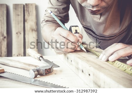 Serious young male carpenter working with wood in his workshop. - stock photo