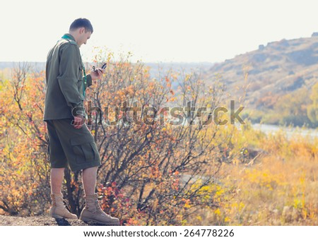 Serious Young Male Scout Navigating a Compass Device for a Direction at the Wilderness - stock photo