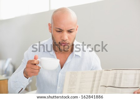 Serious young man having coffee while reading newspaper at home